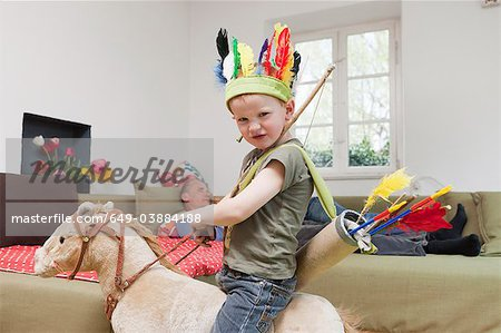 Boy in war bonnet playing with toys Stock Photo - Premium Royalty-Free, Image code: 649-03884188
