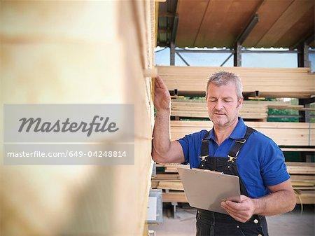 Worker checking wooden planks in joinery Stock Photo - Premium Royalty-Free, Image code: 649-04248814