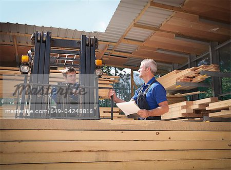 Worker carrying planks on forklift Stock Photo - Premium Royalty-Free, Image code: 649-04248816