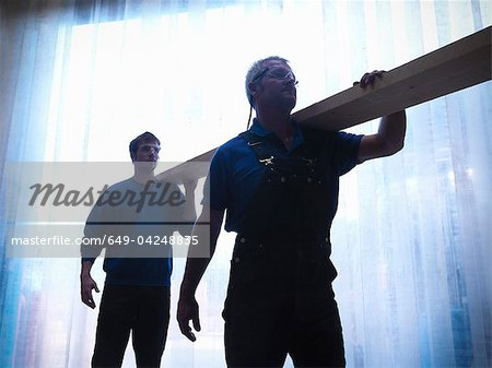 Workers carrying plank of wood together Stock Photo - Premium Royalty-Free, Image code: 649-04248835