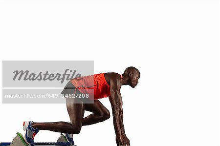 Runner crouched at starting line Stock Photo - Premium Royalty-Free, Image code: 649-04827208