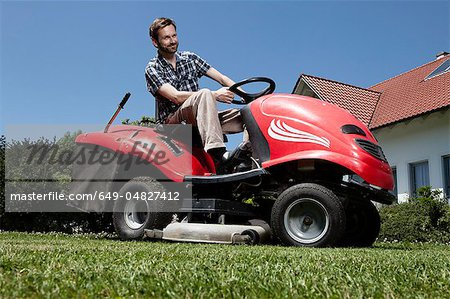 Man riding lawn mower in backyard Stock Photo - Premium Royalty-Free, Image code: 649-04827412