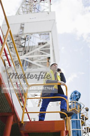 Worker talking on cell phone on oil rig Stock Photo - Premium Royalty-Free, Image code: 649-04827665