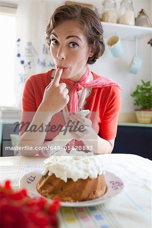 Woman icing a cake in kitchen Stock Photo - Premium Royalty-Free, Image code: 649-05520883