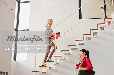 Businesswoman climbing stairs in office Stock Photo - Premium Royalty-Free, Image code: 649-05521387