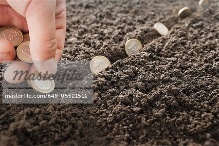 Man planting Euro coins in soil Stock Photo - Premium Royalty-Free, Image code: 649-05521511
