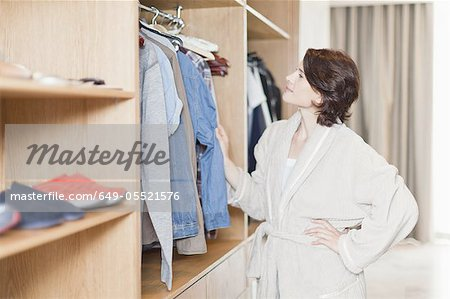 Woman picking clothes out of closet Stock Photo - Premium Royalty-Free, Image code: 649-05521576