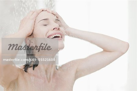 Smiling woman taking shower Stock Photo - Premium Royalty-Free, Image code: 649-05521608