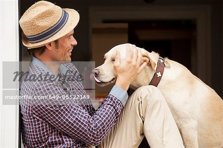 Man petting dog in window Stock Photo - Premium Royalty-Free, Image code: 649-05522149