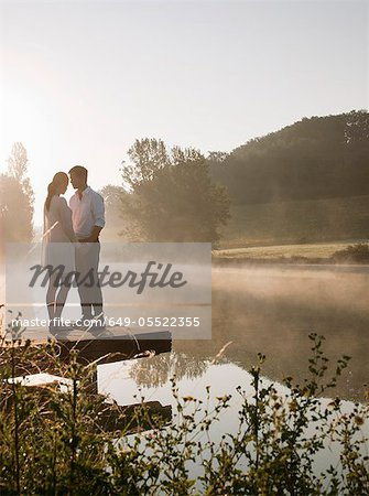 Couple standing on dock of lake Stock Photo - Premium Royalty-Free, Image code: 649-05522355