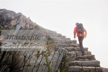 Hiker climbing rocky steps on hillside Stock Photo - Premium Royalty-Free, Image code: 649-05522383