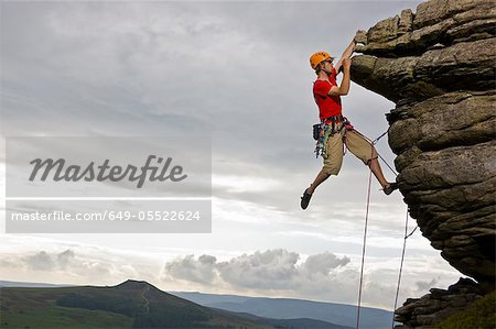 Rock climber scaling steep rock face Stock Photo - Premium Royalty-Free, Image code: 649-05522624