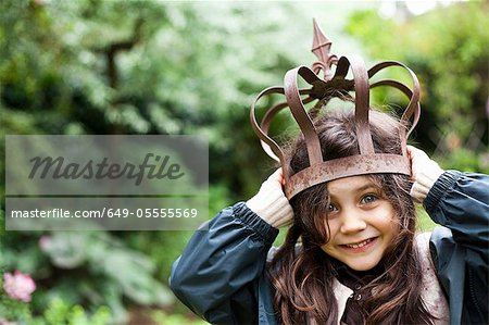 Girl playing with metal crown outdoors Stock Photo - Premium Royalty-Free, Image code: 649-05555569
