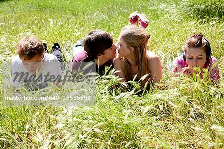 Teenagers ignoring kissing friends Stock Photo - Premium Royalty-Free, Image code: 649-05555599