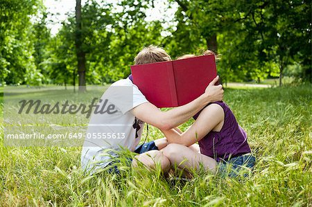 Teenagers hiding behind book in park Stock Photo - Premium Royalty-Free, Image code: 649-05555613