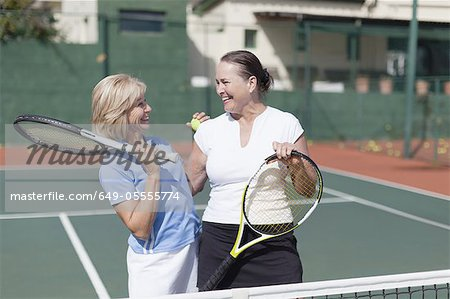 Older women hugging on tennis court Stock Photo - Premium Royalty-Free, Image code: 649-05555774