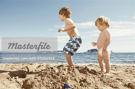 Children stomping on sandcastle Stock Photo - Premium Royalty-Free, Image code: 649-05555923
