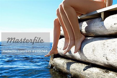 Teenage girls dangling legs over pier Stock Photo - Premium Royalty-Free, Image code: 649-05555960