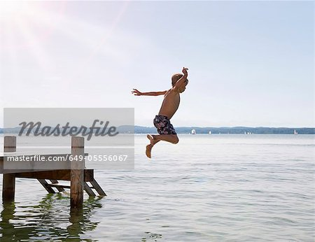 Boy jumping into lake from dock Stock Photo - Premium Royalty-Free, Image code: 649-05556067