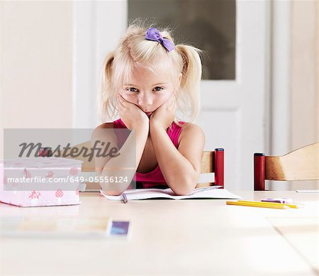 Bored girl doing homework at table Stock Photo - Premium Royalty-Free, Image code: 649-05556124