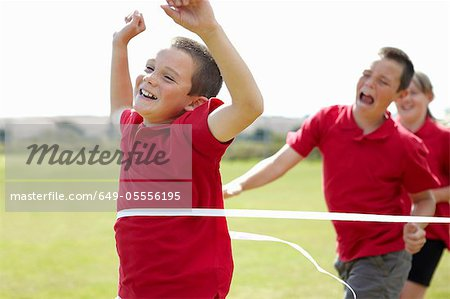 Boy cheering and crossing finish line Stock Photo - Premium Royalty-Free, Image code: 649-05556195