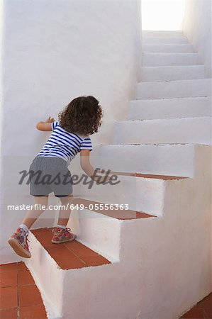 Girl carefully climbing steps Stock Photo - Premium Royalty-Free, Image code: 649-05556363