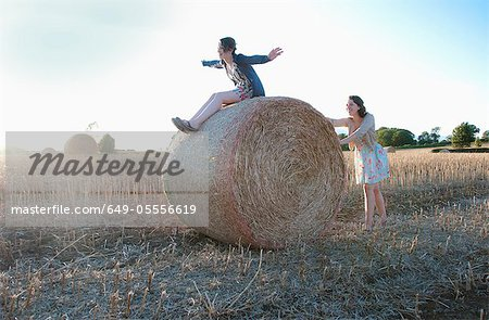 Girls playing on hay bale in field Stock Photo - Premium Royalty-Free, Image code: 649-05556619