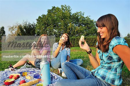 Teenage girls picnicking in rural field Stock Photo - Premium Royalty-Free, Image code: 649-05648922
