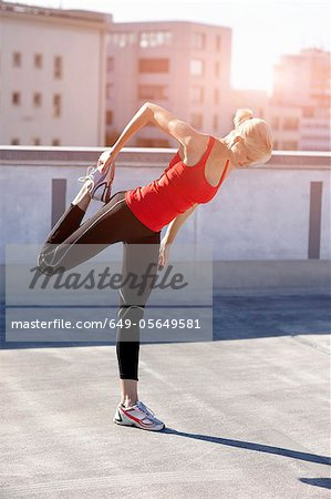 Runner stretching on rooftop Stock Photo - Premium Royalty-Free, Image code: 649-05649581