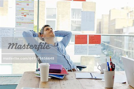 Businessman relaxing at desk in office Stock Photo - Premium Royalty-Free, Image code: 649-05656648