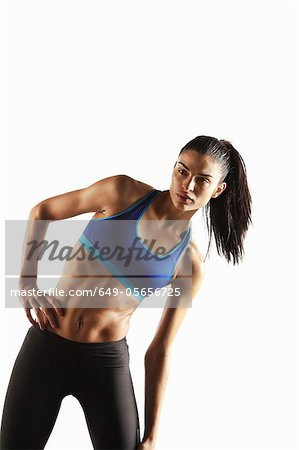 Athlete stretching with hand on hip Stock Photo - Premium Royalty-Free, Image code: 649-05656725