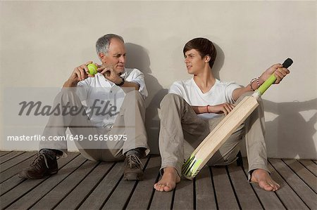 Father and son with cricket bat on patio Stock Photo - Premium Royalty-Free, Image code: 649-05656975