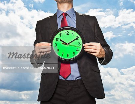 Businessman holding clock Stock Photo - Premium Royalty-Free, Image code: 649-05657041
