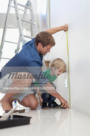 Father and son measuring wall Stock Photo - Premium Royalty-Free, Image code: 649-05657205