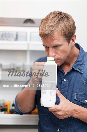 Man smelling milk jug for freshness Stock Photo - Premium Royalty-Free, Image code: 649-05657224