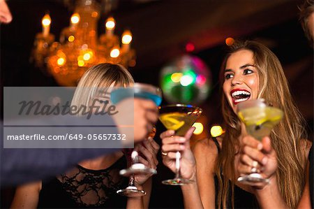 Smiling women having cocktails in club Stock Photo - Premium Royalty-Free, Image code: 649-05657332