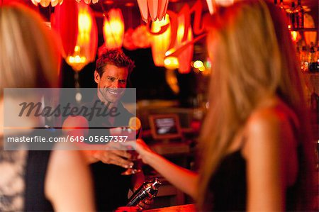 Bartender handing woman a cocktail Stock Photo - Premium Royalty-Free, Image code: 649-05657337