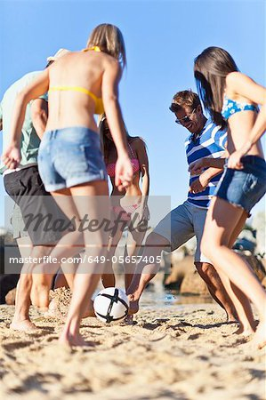 Friends playing soccer on beach Stock Photo - Premium Royalty-Free, Image code: 649-05657405