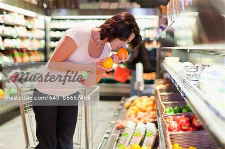 Woman smelling fruit at grocery store Stock Photo - Premium Royalty-Free, Image code: 649-05657455