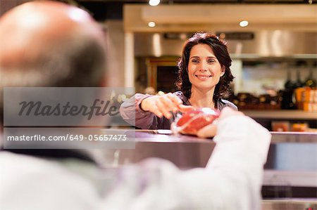 Woman buying meat from butcher Stock Photo - Premium Royalty-Free, Image code: 649-05657473