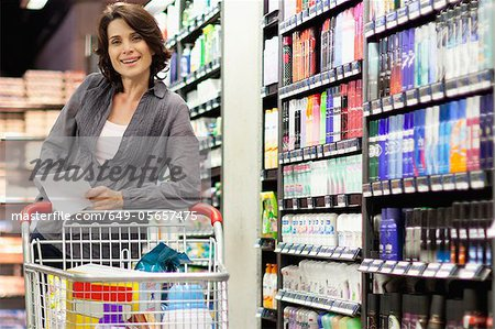 Smiling woman grocery shopping Stock Photo - Premium Royalty-Free, Image code: 649-05657475