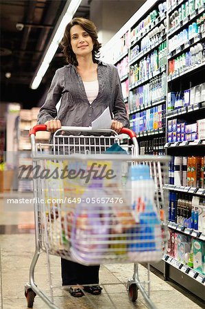Smiling woman grocery shopping Stock Photo - Premium Royalty-Free, Image code: 649-05657476
