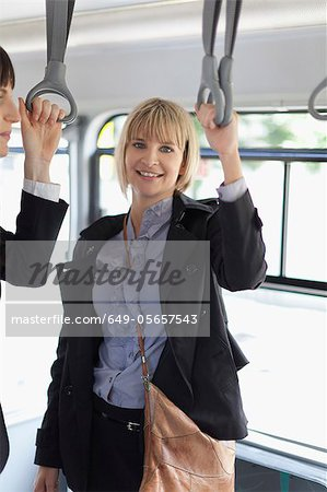 Smiling businesswomen riding the bus Stock Photo - Premium Royalty-Free, Image code: 649-05657543