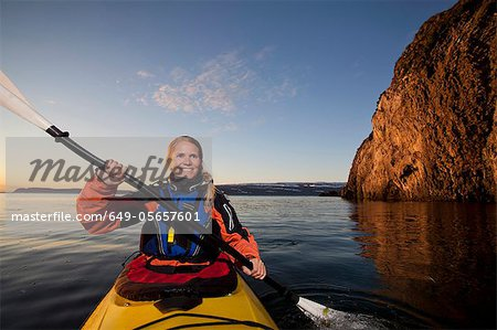 Woman kayaking in still lake Stock Photo - Premium Royalty-Free, Image code: 649-05657601