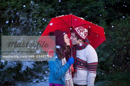 Smiling couple under umbrella in snow Stock Photo - Premium Royalty-Free, Image code: 649-05657766
