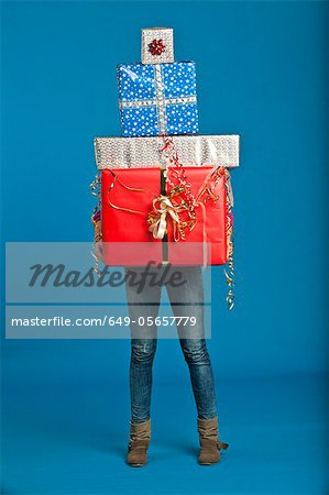 Woman carrying wrapped gifts Stock Photo - Premium Royalty-Free, Image code: 649-05657779