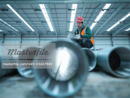 Worker examining pipes in warehouse Stock Photo - Premium Royalty-Free, Image code: 649-05657969