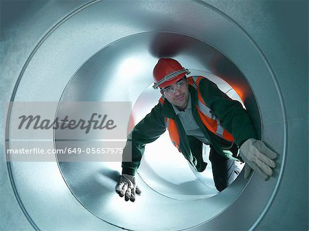 Worker climbing in steel piping Stock Photo - Premium Royalty-Free, Image code: 649-05657975