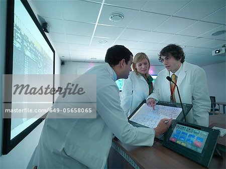 Scientists discussing chart in meeting Stock Photo - Premium Royalty-Free, Image code: 649-05658065