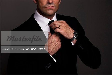 Businessman adjusting his tie Stock Photo - Premium Royalty-Free, Image code: 649-05658213